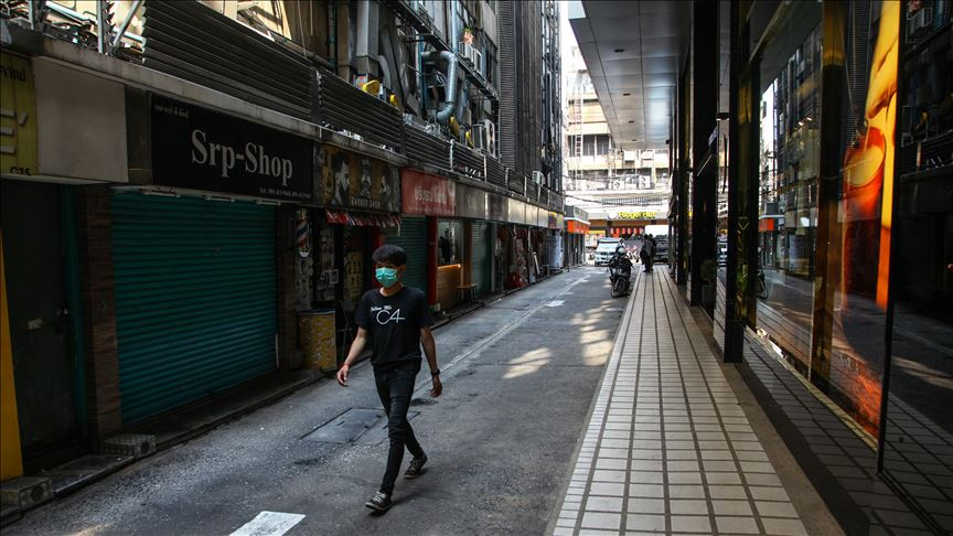 Man wearing face mask walking down an alley of closed shops