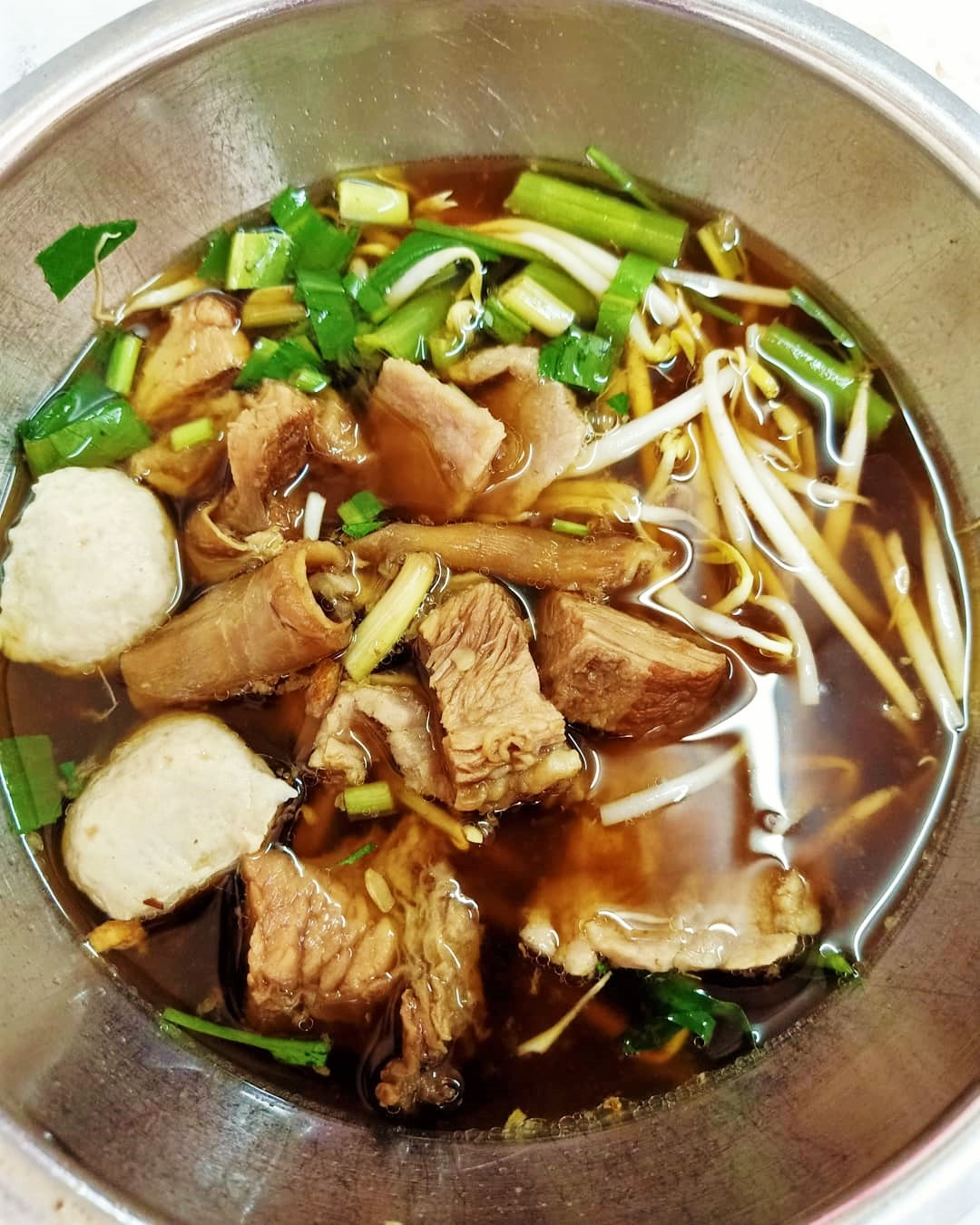 Beef balls, tendon, brisket, bean sprouts in a bowl of beef broth
