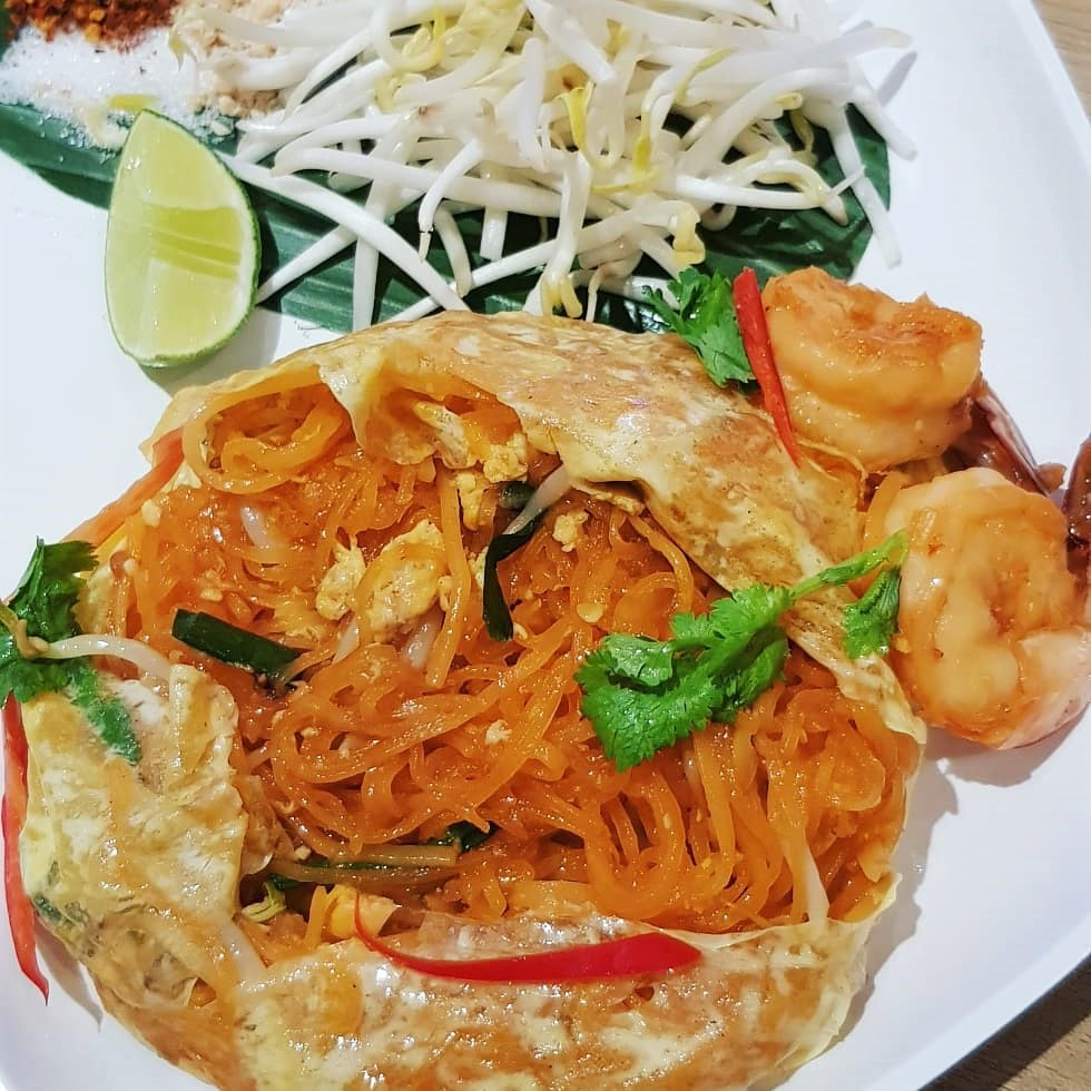 Pad thai covered in thin fried egg with shrimp and bean sprouts